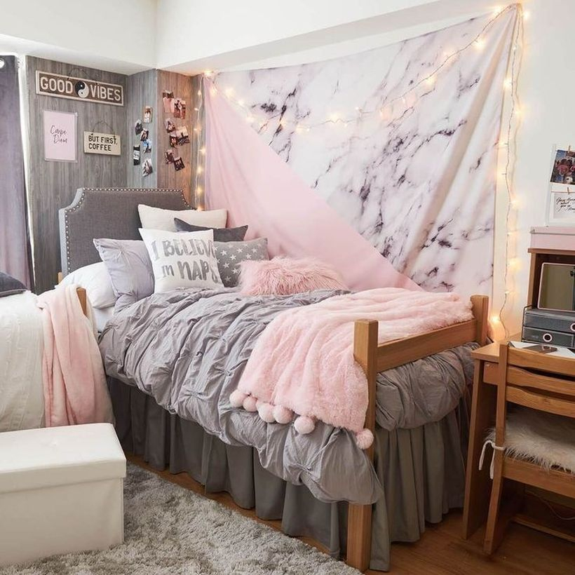 Small girls room decor with a gray bed combined with a small pink blanket, gray and white pillows, string lights to complement the decor