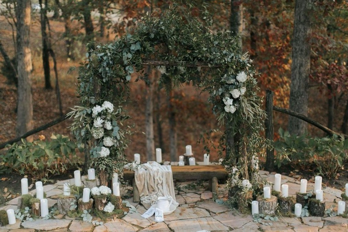 An elegant take on rustic wedding style with arrangement candle, greenery, flowers, and a hint of moss