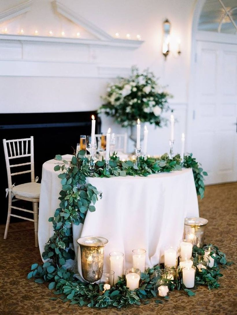 Romantic sweetheart table with lush greenery accents and a grouping of candles