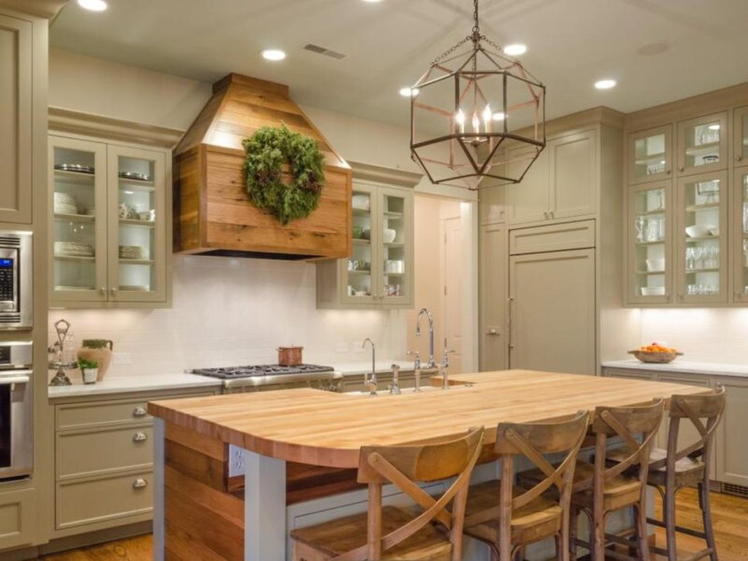 Beautiful kitchen with unique candle lamp, wooden island table and wooden chairs to look awesome