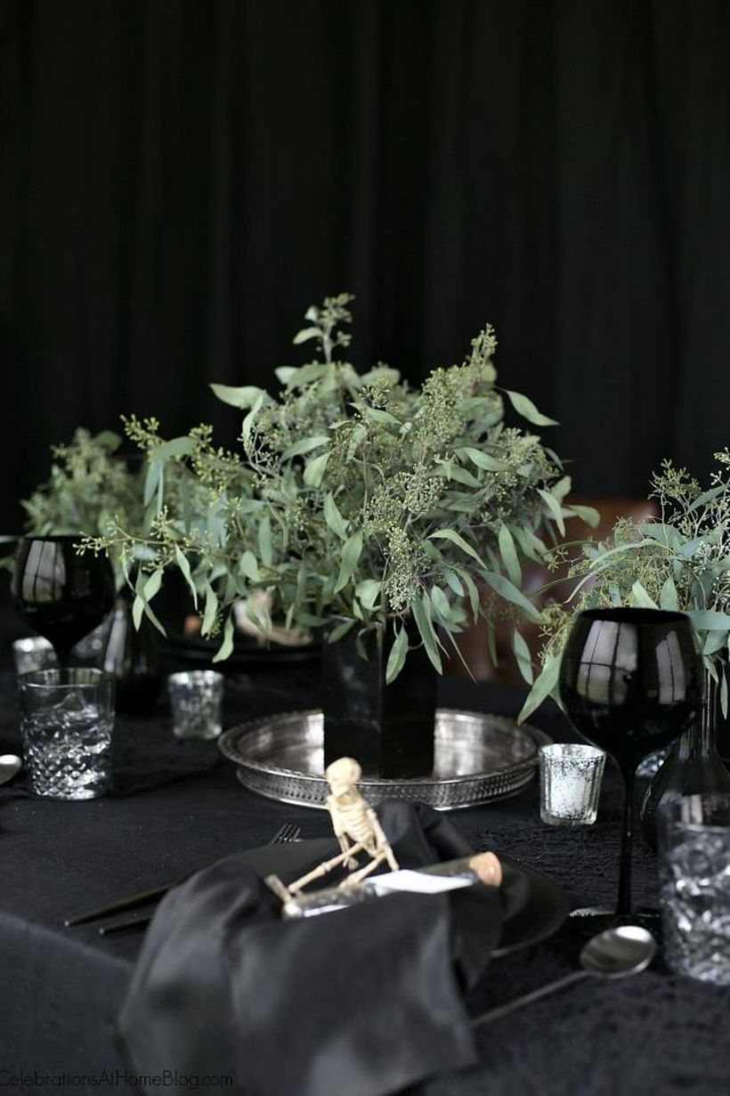Creepy dining table with dark theme and small human skeleton ornament