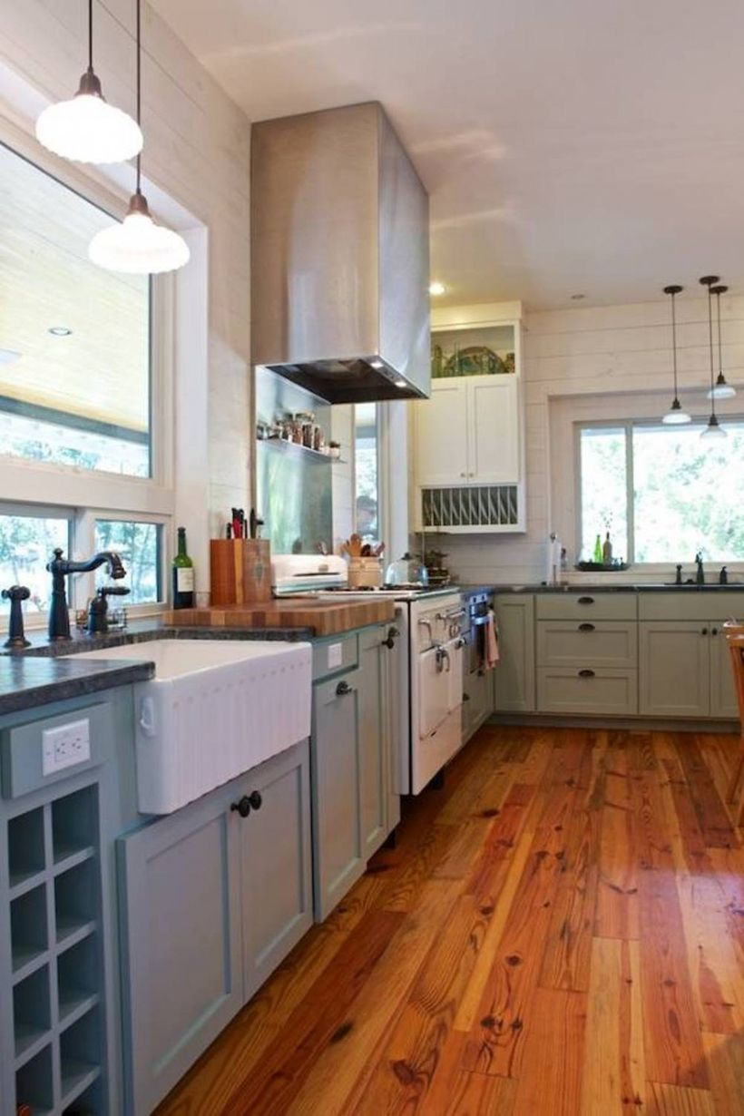 Hardwood floor kitchen style with gray cabinet, white walls and hanging light