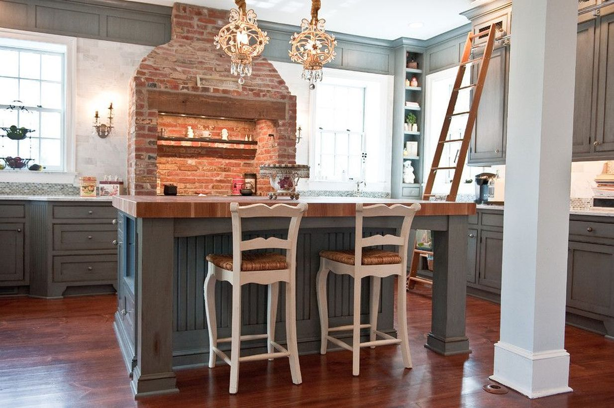 Simple wooden kitchen flooring with gray cabinet, gray wooden island table and brick cooker hood