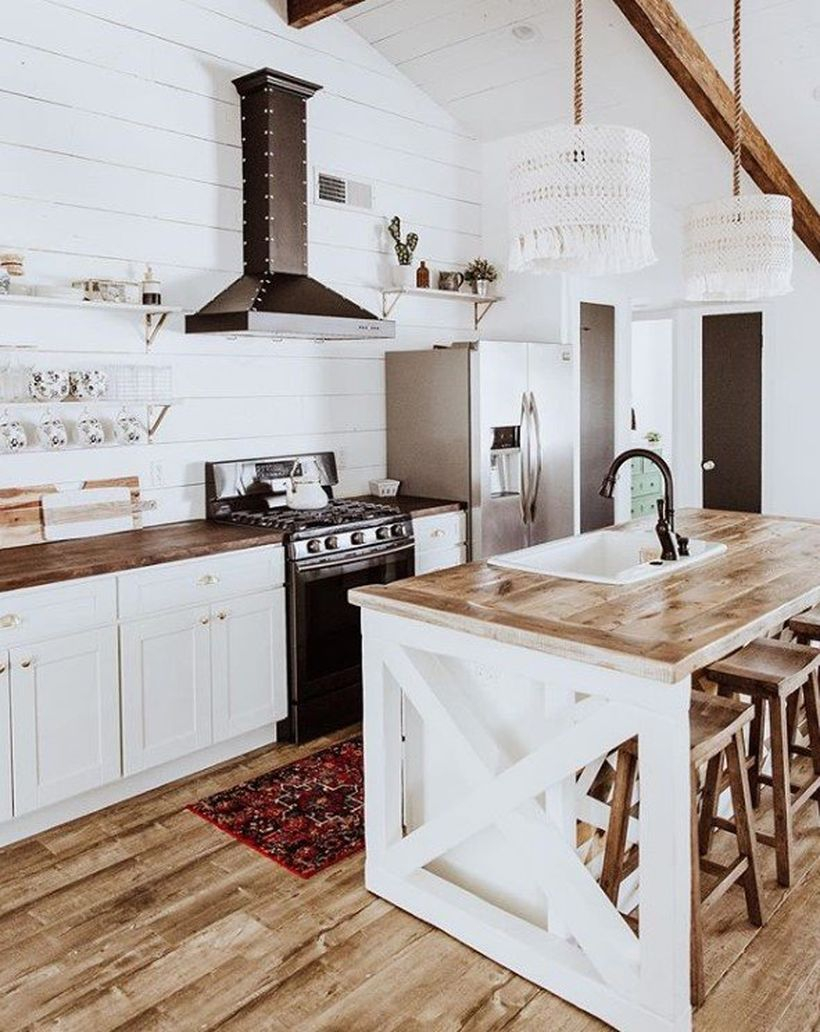 White kitchen with white hanging plants, wooden table and white cabinet to look stunning