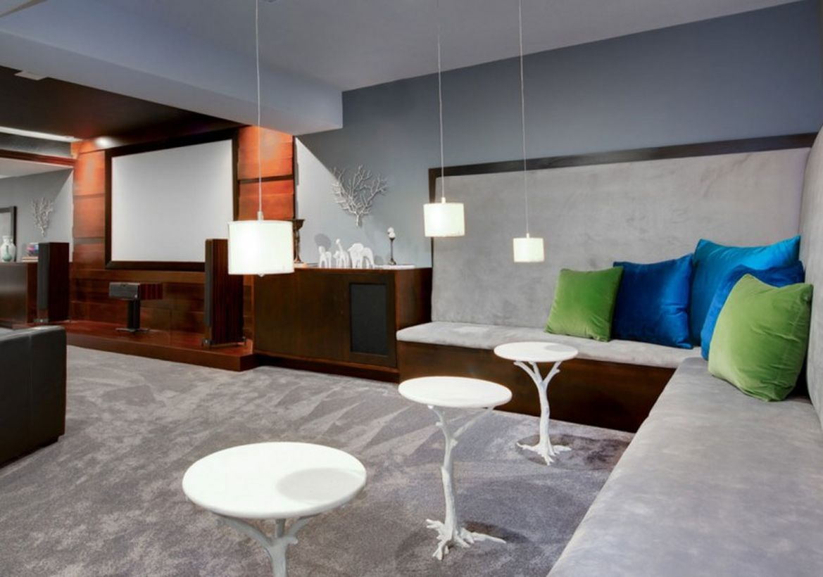 Basement with small hanging lamps, smal round white table and gray carpet