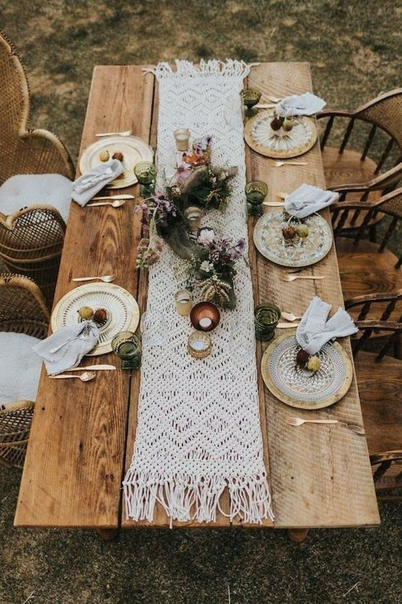 Boho chic wedding table setting with a macrame table runner, dyed napkins, lush florals and greenery, gilded plates and candles