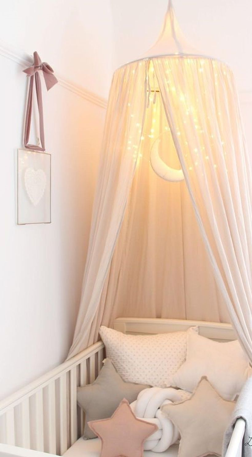 White-dreamy-baby-girls-nursery-room-with-hanging-baby-mosquito-nets-and-decorative-lighting-like-the-moon-and-stars