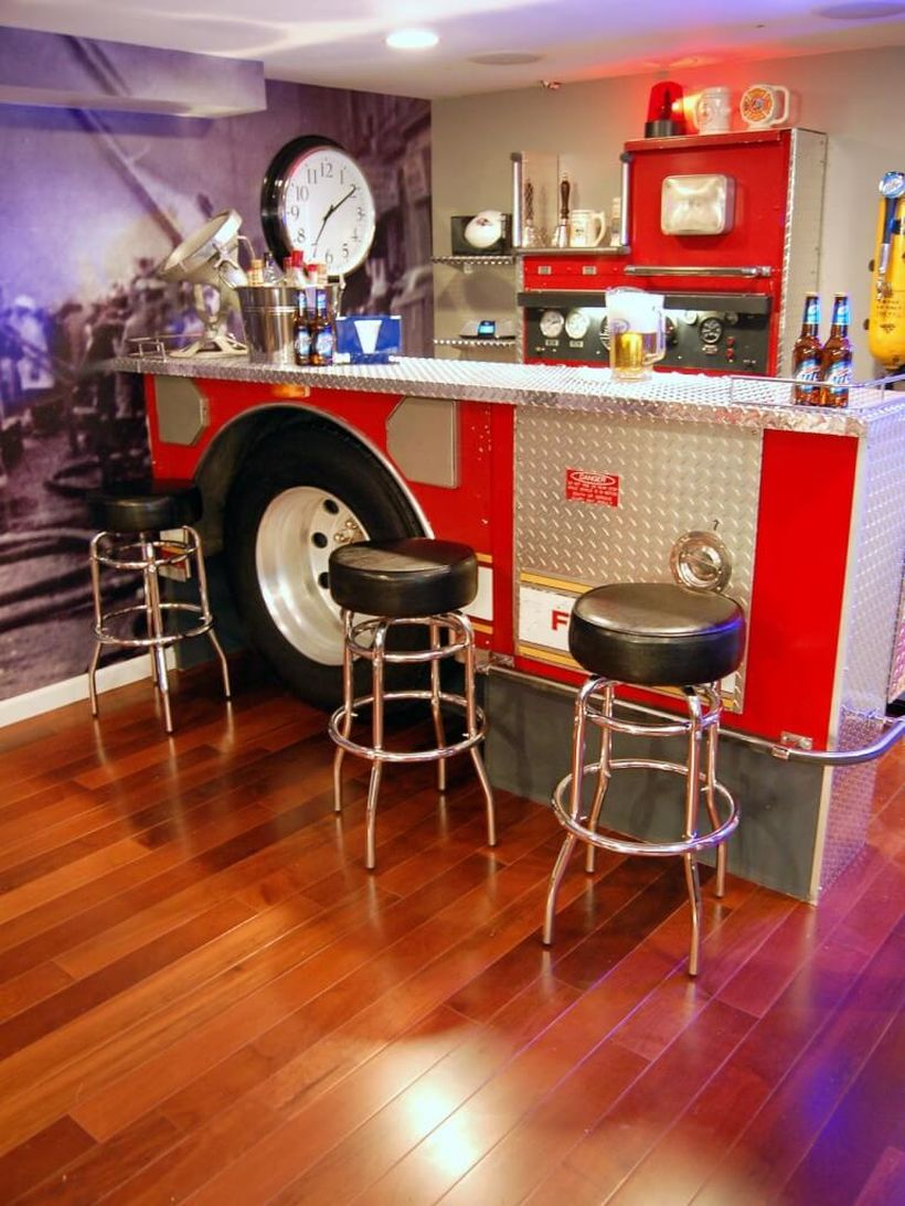 Car-shaped coffee bar made of red white metal and a small black sofa that looks cool