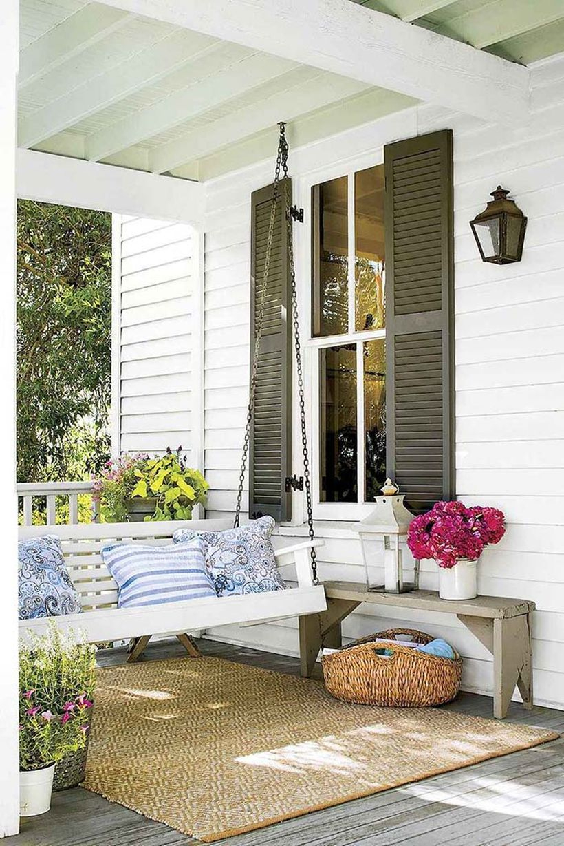 High-ceiled front porch idea decor with white swing bed