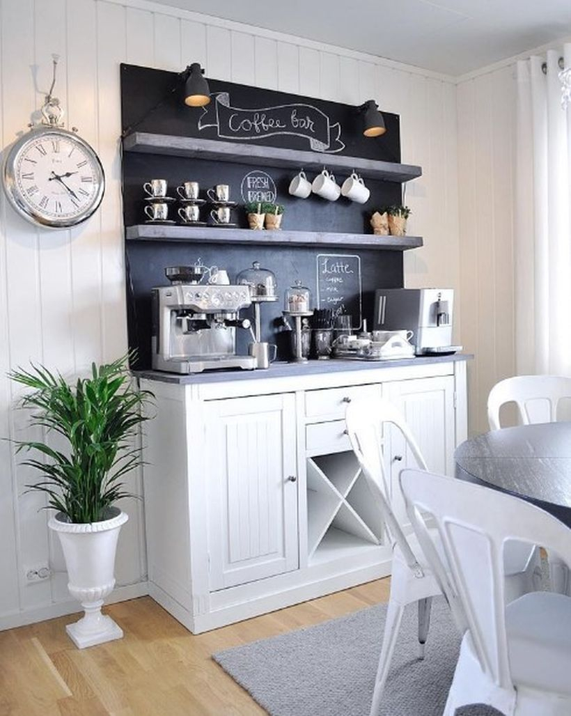 White coffee bar with black board, black shelf and added green plants in a white pot