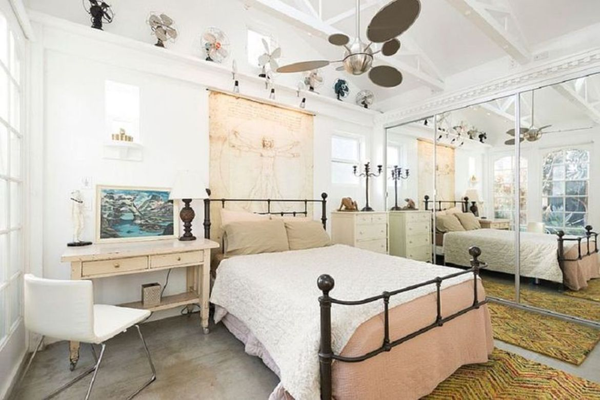 Black-iron-frame-bed-and-wooden-white-nightstand-yang-menghiasi-your-bedroom-with-hanging-rack-to-store-classic-fan-and-classic-table-lamp-menciptakan-suasana-vintage