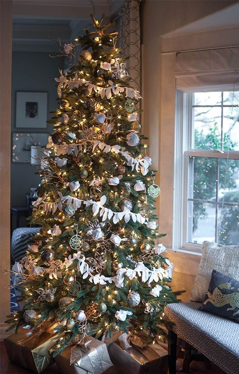 Green-christmas-tree-decoration-with-various-ornaments-that-are-characteristic-of-christmas-and-wrapped-in-white-crepe-paper-to-make-it-interesting