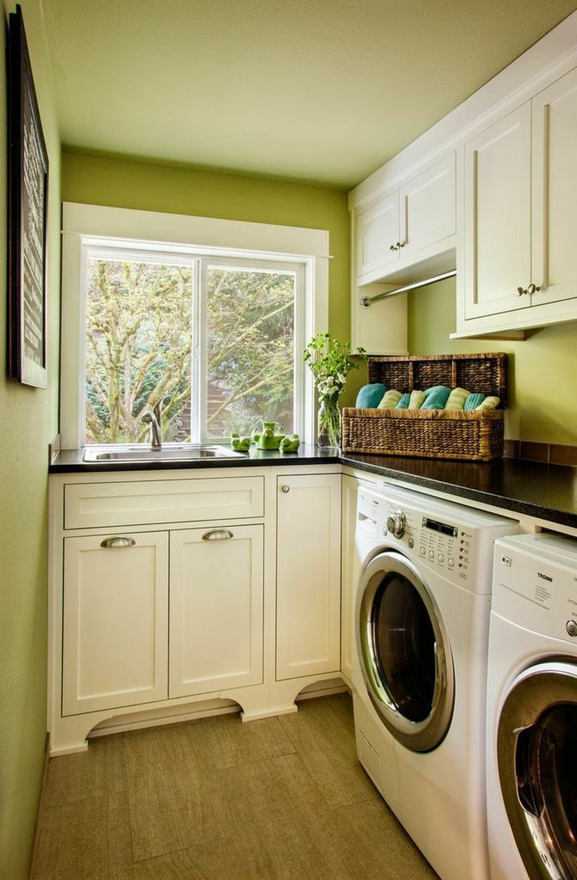Laundry room with white cabinet and green walls