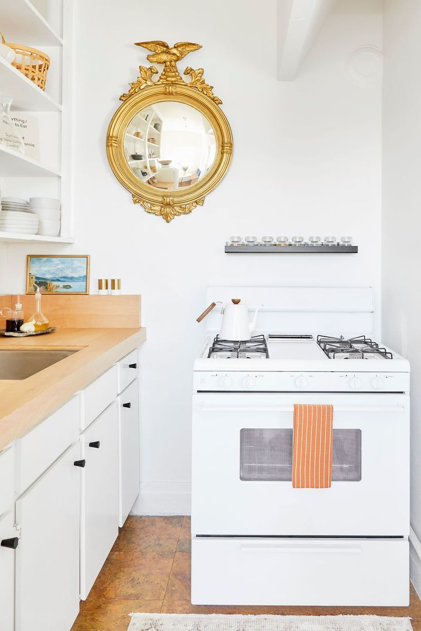 Minimalist-white-kitchen-design-with-modern-stove-and-round-gold-mirror-to-decorate-your-kitchen-in-the-small-space