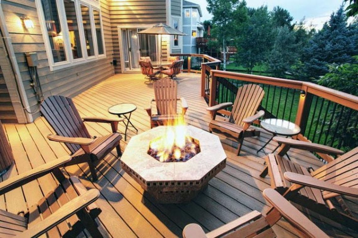 Simple-backyard-patio-deck-design-with-a-unique-hexagon-shaped-fire-pit-wooden-chair-and-coffee-table-to-relax-and-warm-the-body