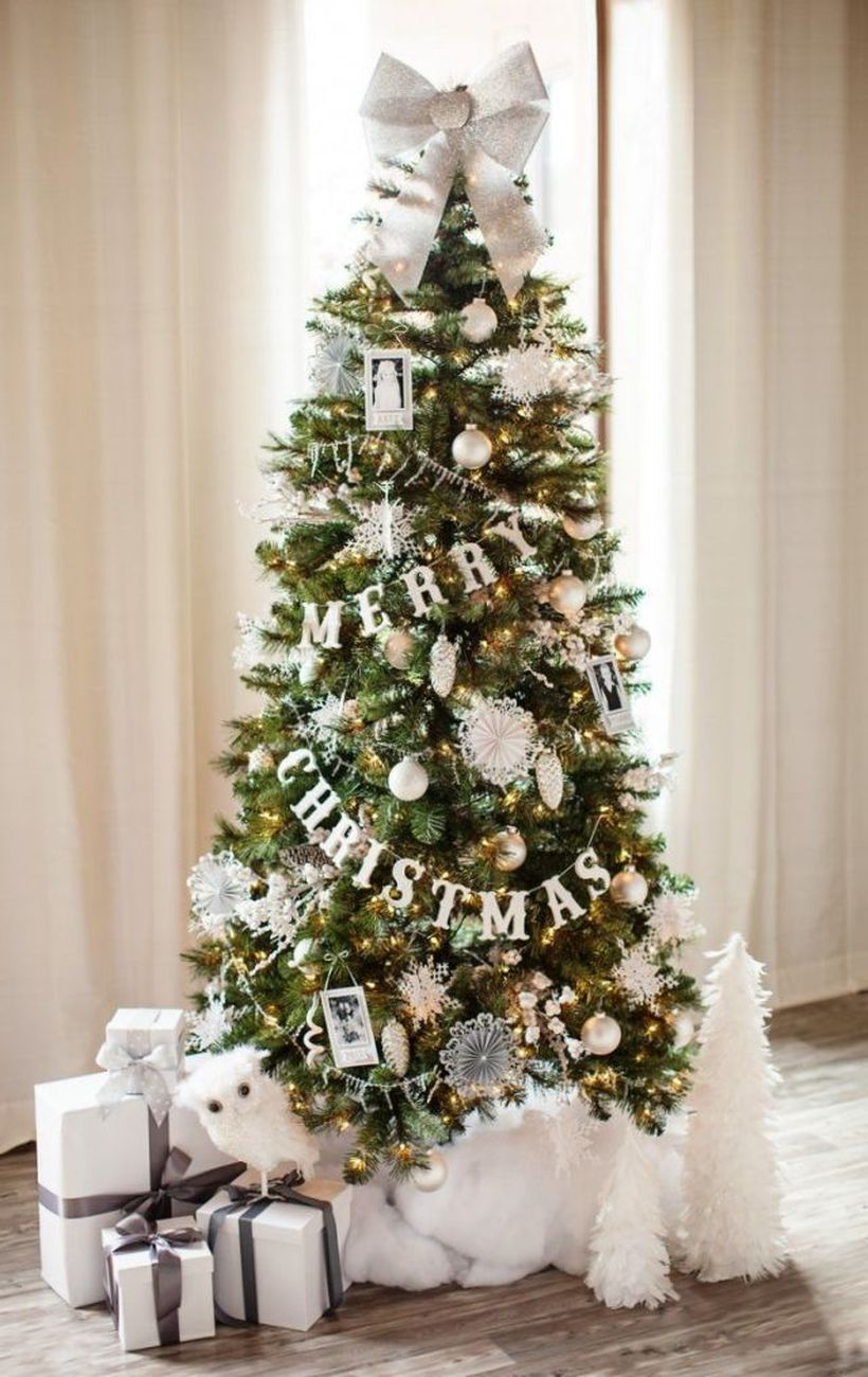 Small-green-christmas-tree-with-pine-ornaments-snow-ornament-and-large-ribbon-at-the-top-to-beautify-the-tree-decorations