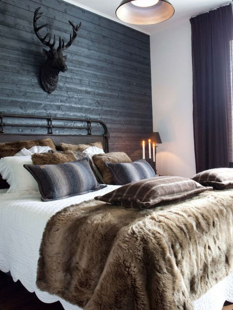 Bedroom with a black wooden wall, dark textiles
