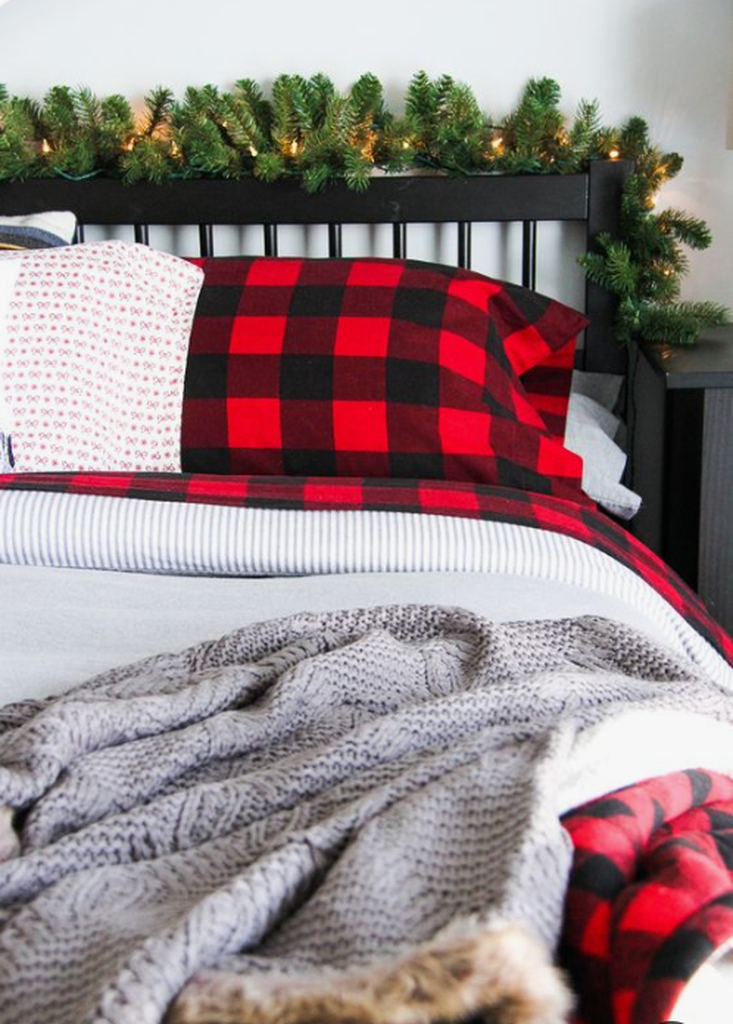 Bedroom with plaid and knit bedding, evergreens