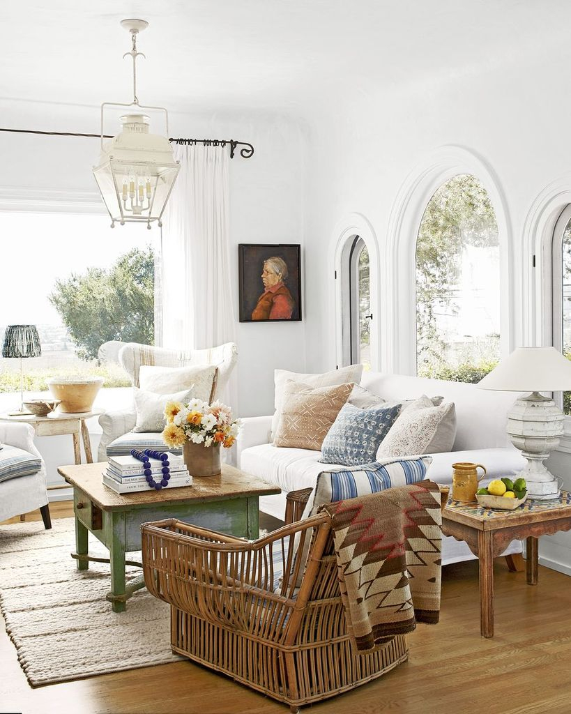 Bright farmhouse living room with wooden table, white sofa and rattan chair to make more elegant your living room