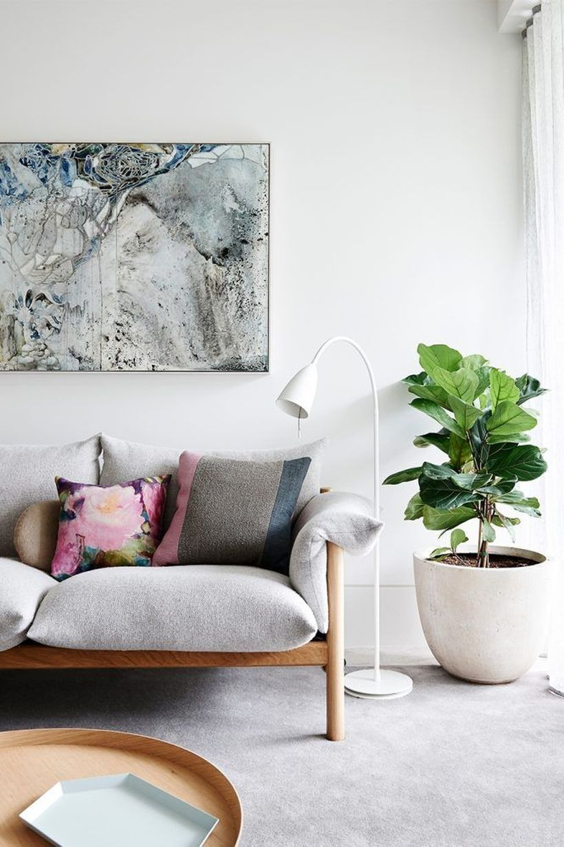 Colorful cushion with flower pattern above white sofa