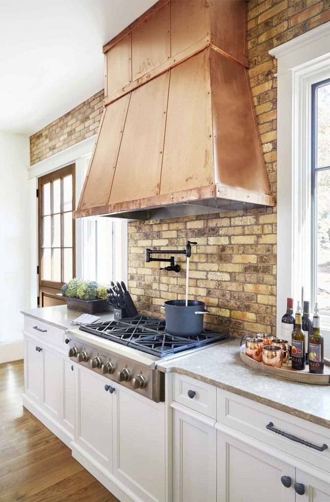 Kitchen design with brick walls and white cabinets
