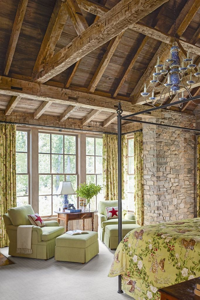 Rustic bedroom combined with stone walls, high wooden-beamed ceilings