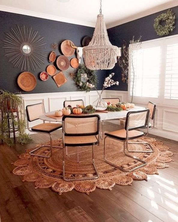 A-bright-boho-dining-room-with-a-beaded-chandelier-wicker-chairs-a-jute-rug-decorative-plates-and-greenery