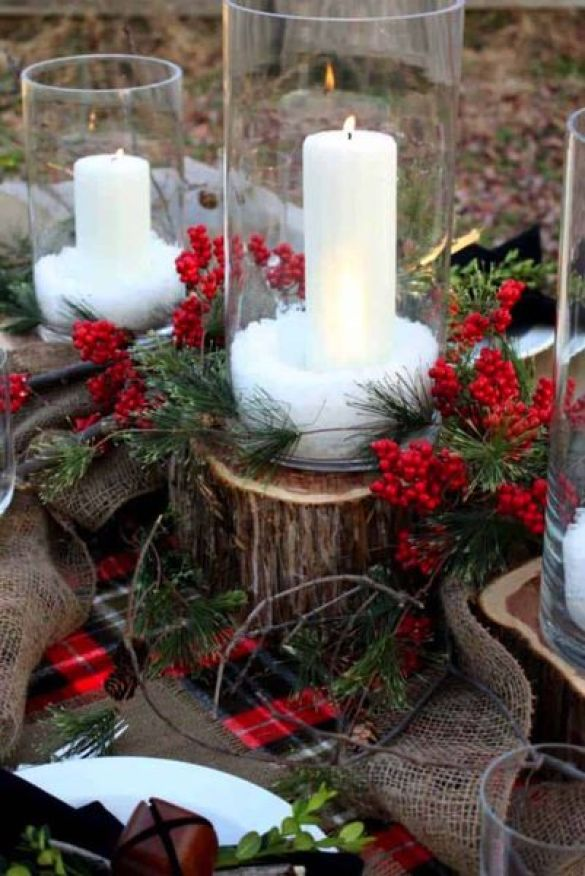 A-centerpiece-of-fresh-sprigs-of-greenery-and-candles-in-glass-vases.