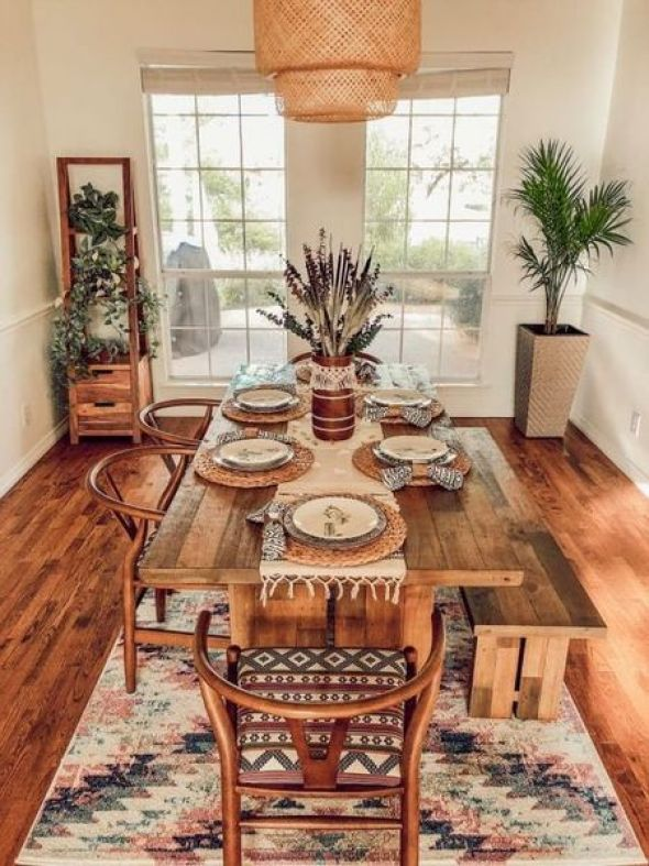 A-gorgeous-boho-dining-space-with-potted-greenery-a-boho-rug-a-wicker-pendant-lamp-and-warm-stained-furniture