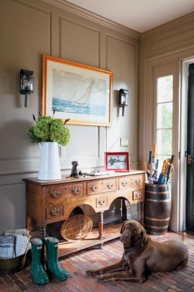 A vintage farmhouse entryway with a large refined console, a brick floor, a seascape and a jug with green hydrangeas