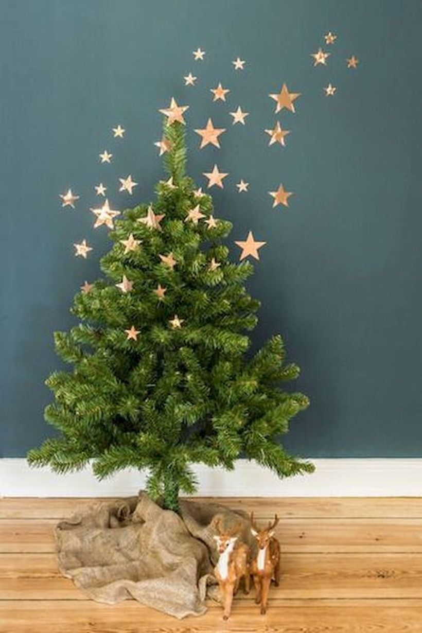 11-a-small-christmas-tree-with-burlap-on-the-floor-and-copper-foli-stars-as-decor-going-up-to-the-wall