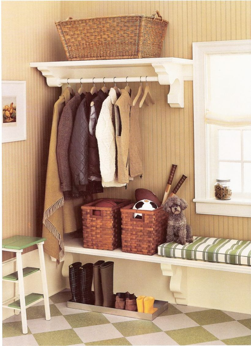 Mounted-wooden-bench-seat-with-cushion-above-shoe-and-boots-tray-storage-plus-rattan-basket-storage-under-clothing-hooks-in-the-corner-ideas-783x1078
