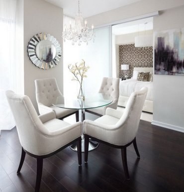 Contemporary-dining-room-with-rounded-glass-table-and-cozy-dining-chairs