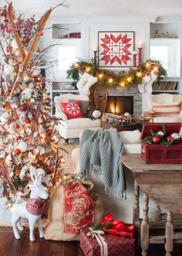 1 a-bold-and-creative-christmas-living-room-with-a-white-tree-with-red-and-white-ornaments-and-skis-a-fir-garland-with-lights-red-candleholders-and-a-red-box-with-ornaments