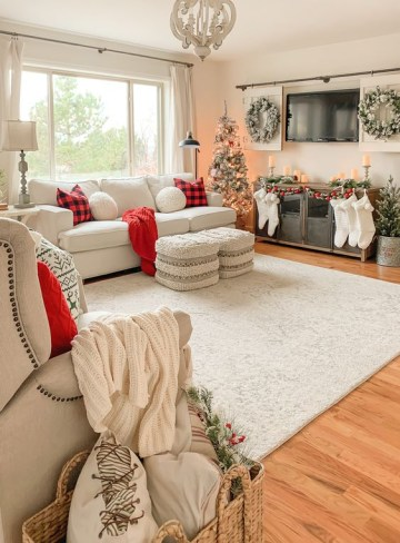 1 farmhouse-christmas-decor-with-white-stockings-red-plaid-pillows-and-red-blankets-flocked-wreaths-and-flocked-christmas-trees-plus-candles
