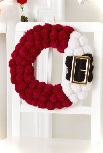 2-06-a-red-black-and-white-pompom-santa-inspired-wreath-with-a-large-buckle-is-a-fun-idea-instead-of-a-usual-greenery-one