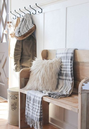 38-simple-farmhouse-entryway-is-perfectly-decorated-for-winter-with-large-coat-hooks-a-rustic-bench-and-a-place-for-snow-covered-boots