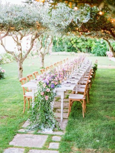 A-beautiful-outdoor-spring-wedding-reception-with-pink-blooms-hanging-on-the-trees-a-lush-table-runner-of-bright-blooms-and-greenery