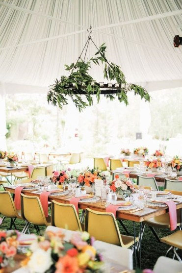 A-bright-spring-wedding-reception-with-a-greenery-chandelier-bright-linens-and-chairs-and-colorful-blooms
