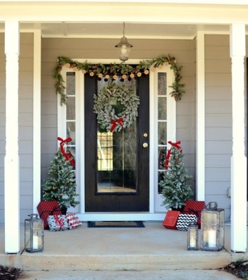 A-cozy-christmas-front-porch-with-an-evergreen-and-pinecone-garland-a-snowy-wreath-mini-trees-with-lights-and-lots-of-gift-boxes