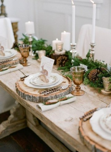 A-gorgeous-rustic-christmas-table-with-an-evergreen-and-pinecone-runner-amber-glasses-wood-slice-placemats-tall-candles-and-deer-cards