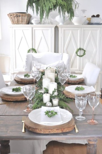 A-rustic-christmas-tablescape-with-wood-slice-chargers-an-evergreen-runner-candles-and-ornaments-plus-some-greenery