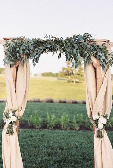 Classic-fabric-draped-arch-topped-with-lush-eucalyptus-leaves