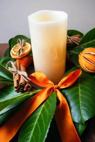 Decoration-table-automne-bougie-cylindrique-feuilles-vertes-noeud-orange-bâtons-cannelles-tranches-agrumes-683x1024