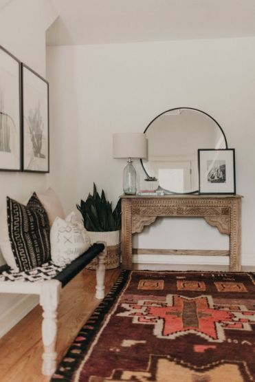04-a-boho-entryway-with-a-vintage-encrusted-console-a-woven-bench-pillows-artworks-and-succulents