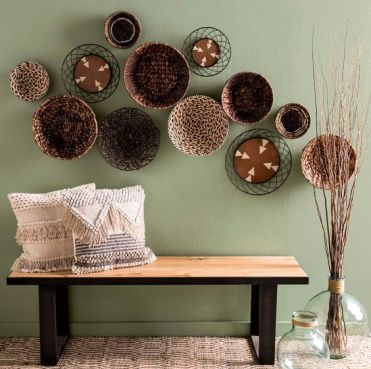 23-a-wood-and-metal-bench-woven-and-fringe-pillows-an-arrangement-of-plates-and-some-branches
