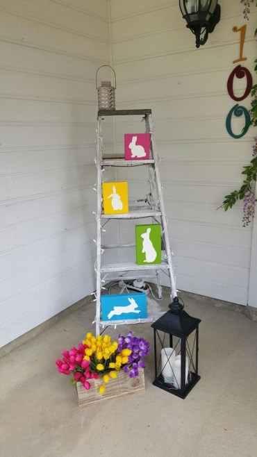 A-ladder-with-colorful-bunnies-a-lantern-with-candles-and-colorful-potted-tulips-in-a-wooden-planter