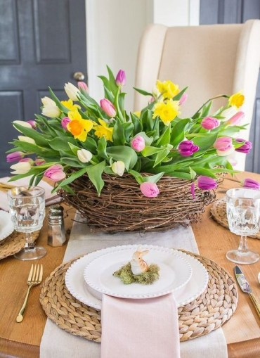A-large-nest-with-bright-tulips-and-daffodils-moss-with-bunnies-and-wicker-chargers-for-a-spring-table