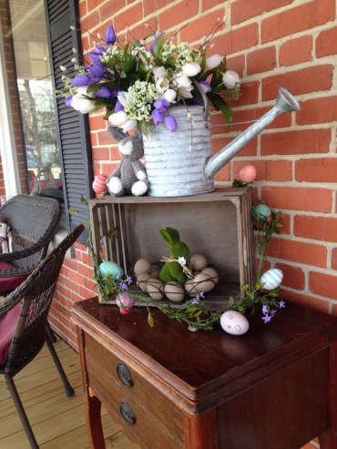 A-simple-easter-decoration-of-a-crate-with-colorful-eggs-a-watering-can-with-a-spring-bloom-arrangement-and-bunnies