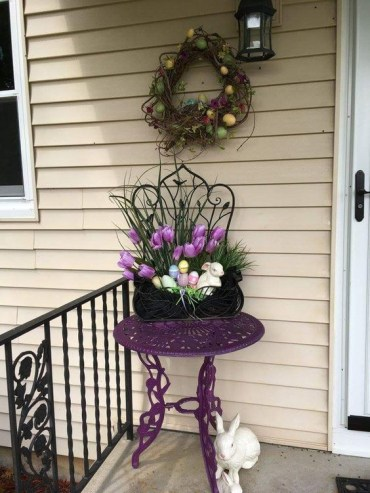 A-vine-wreath-with-colorful-eggs-potted-blooms-and-faux-eggs-in-a-planter-fake-bunnies-for-porch-decor